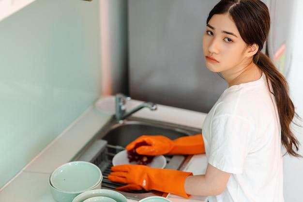 アジアの女性は疲れた気分で皿洗いをしています