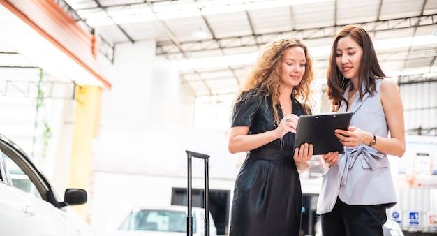 新しい車を引き渡す前に、笑顔で幸せな白人女性のクライアントに保険について話し、説明するアジアの女性営業担当者。カーリースおよびディーリング事業。