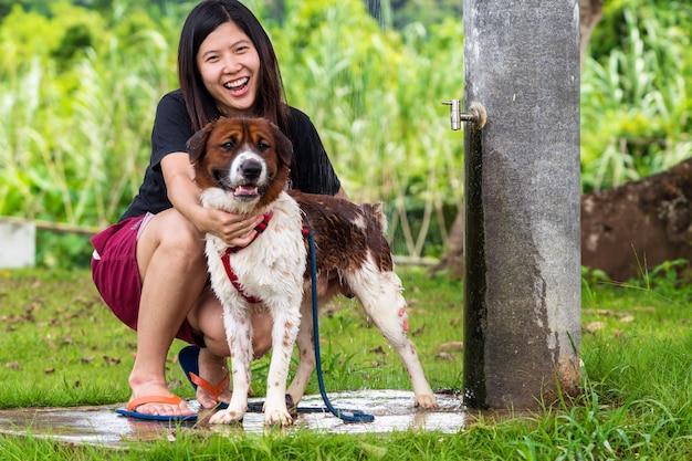 Азиатские женщины делают душ для собаки смешанной породы коричневого цвета с белым цветом, стоящего на курорте, ло