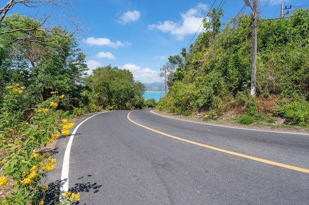 여름 시즌에 푸켓 섬 주변의 아스팔트 도로 푸켓 태국에서 아름다운 푸른 하늘 배경입니다.
