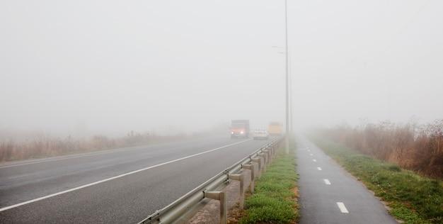 街の外のアスファルト道路と朝の濃い霧