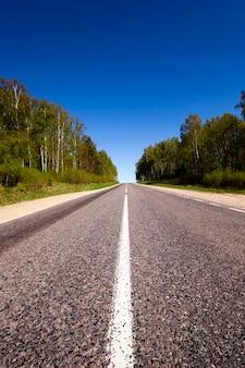 Асфальтированная дорога - небольшая сельская асфальтированная дорога, сфотографированная в летнее время года.
