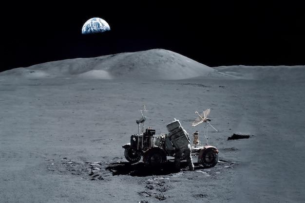 Космонавт выполняет манипуляции на поверхности луны. элементы этого изображения были предоставлены наса. фото высокого качества