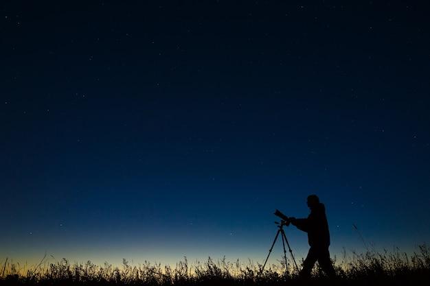 Астроном фотографирует ночное звездное небо на цифровой фотоаппарат с помощью штатива.