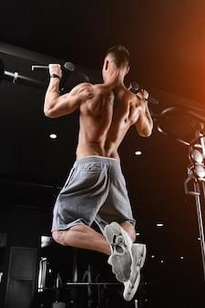 운동 선수는 턱걸이를합니다-체육관의 턱, 스포츠 바디 토플리스 모델. 뒤에서 슛, 낮은 키,