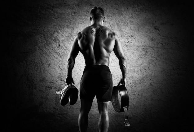 Спортсмен идет в тренажерный зал на тренировку. в руках он держит кроссовки и ремень. вид сзади