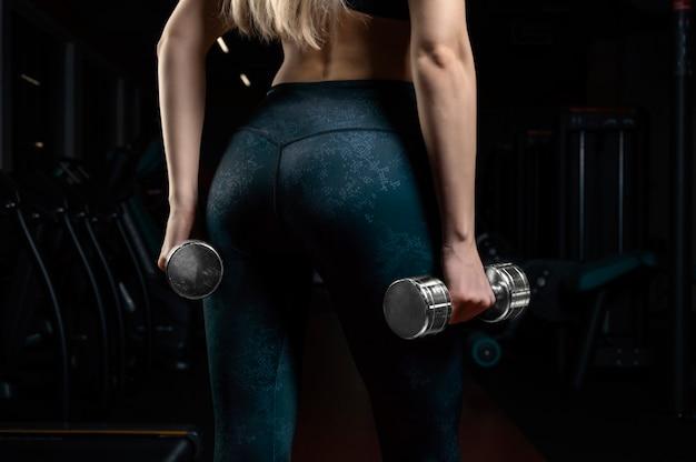 운동 선수는 그녀의 손에 아령을 들고 체육관에 서 있습니다. 뒷모습. 스포츠, 보디 빌딩, 피트니스의 개념. 혼합 매체