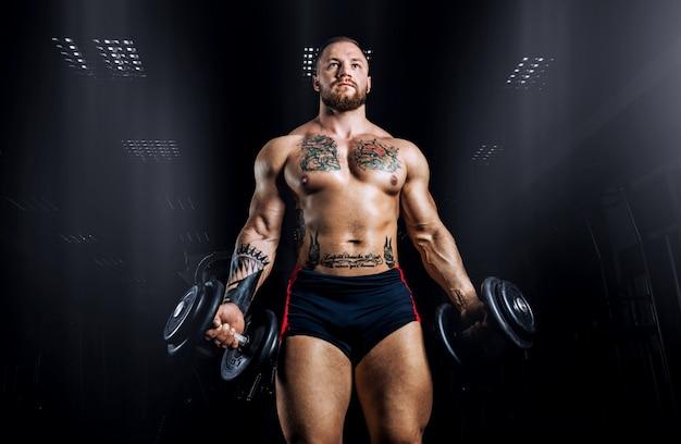 Спортсмен стоит с двумя гантелями в руках. передний план