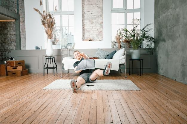 운동 선수는 베개로 바닥에 누워 침실에서 즐겁게 놀고, 배경에는 침대, 꽃병, 카펫이 있습니다.