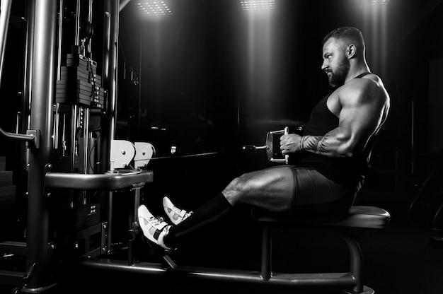 Спортсмен выполняет упражнение на широчайшие мышцы спины на специальном приспособлении. вид сбоку