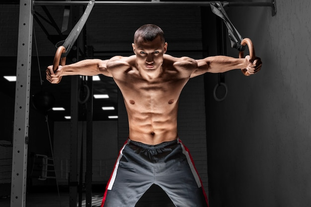 Спортсмен подтягивается на гимнастических кольцах.