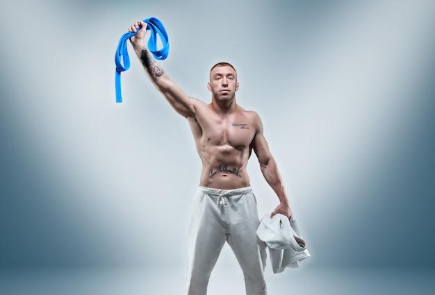 アスリートは意気揚々と青いベルトを持ち上げます。空手、サンボ、柔術のコンセプト。ミクストメディア
