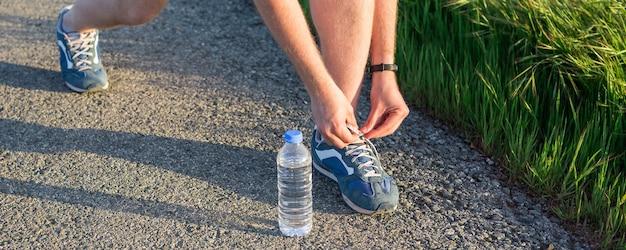 운동선수가 신발끈을 묶고 있습니다. 스포츠 및 실행 아이디어 개념입니다. 신발 끈을 묶는 젊은 남자 주자