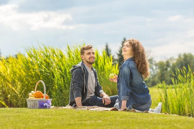 魅力的なカップルは果物のバスケットを持って草の上に座っています