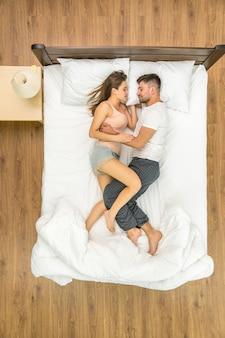ベッドで寝ている魅力的なカップル。上から見る