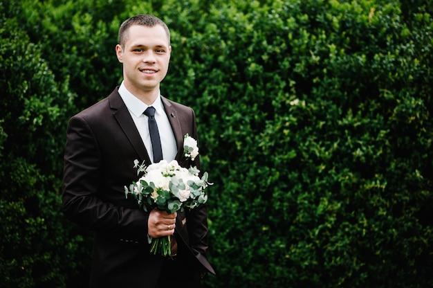スーツを着た魅力的な新郎と花束の花のネクタイ、そしてジャケットのブートニアまたはボタンホール。