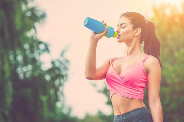매력적인 운동가는 햇빛 배경에서 물을 마신다