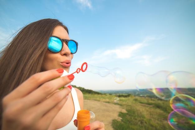 Привлекательная женщина пускает пузыри на фоне голубого неба