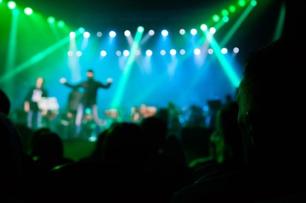 Публика на концерте на фоне сцены.