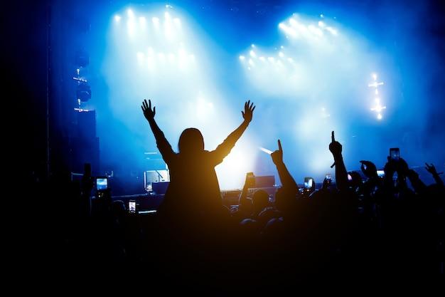콘서트의 관객은 즐깁니다. 제기 손과 스마트 폰의 실루엣입니다.