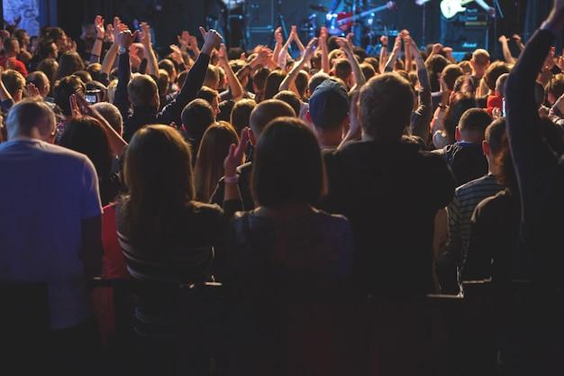 大きなコンサートクラブのステージでコンサートを見ている聴衆。