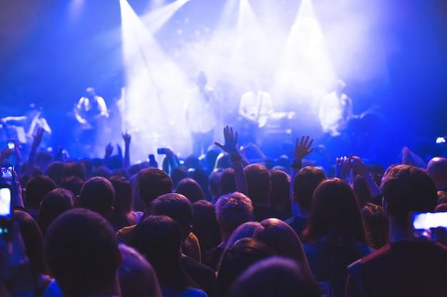 夜のコンサートクラブのステージでコンサートを見ている聴衆。