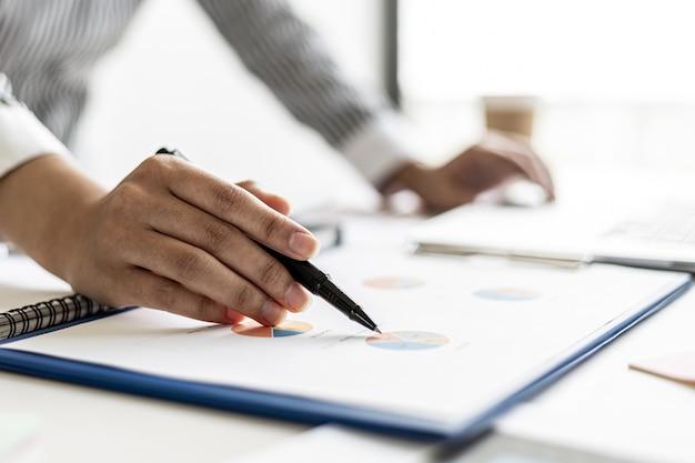 감사인은 재무 제표를 가리키고 재무 부서에서 준비한 문서의 재무 정보를 검토한 후 회의에서 경영진에게 제출합니다.
