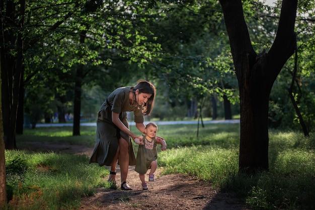 女の赤ちゃんが最初の一歩を踏み出し、若い母親が子供を手に持って、緑の木々や草に囲まれた公園の小道を歩くのを手伝ってくれます。親のケア
