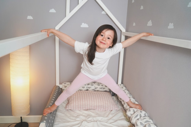 赤ちゃんは寝る前に彼のベッドでジャンプしています。うれしそうな女の子がベッドにふける。白いtシャツとピンクのレギンスの幼児