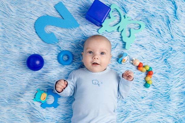 아기는 장난감, 개발 및 게임의 개념 중 집에서 파란색 매트에 누워 있습니다.
