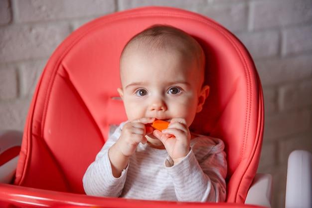 Ребенок сидит на стульчике и ест морковь