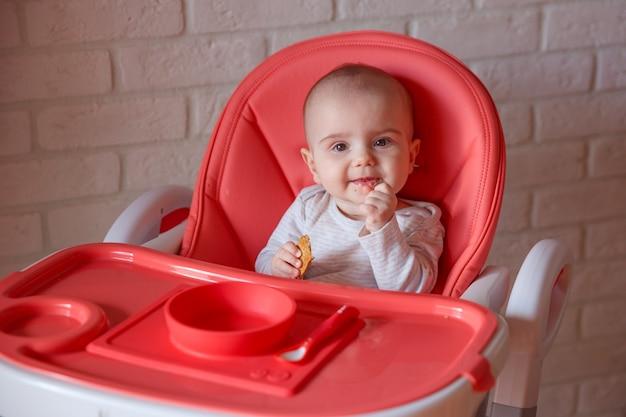 Ребенок сидит на высоком стульчике и ест