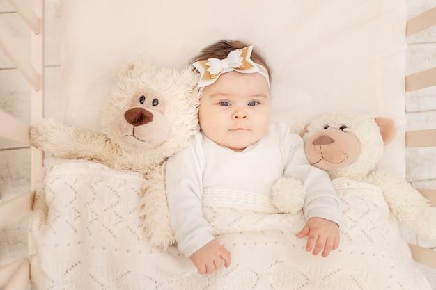 赤ちゃんはテディベアと白いボディスーツのベビーベッドで生後6ヶ月です