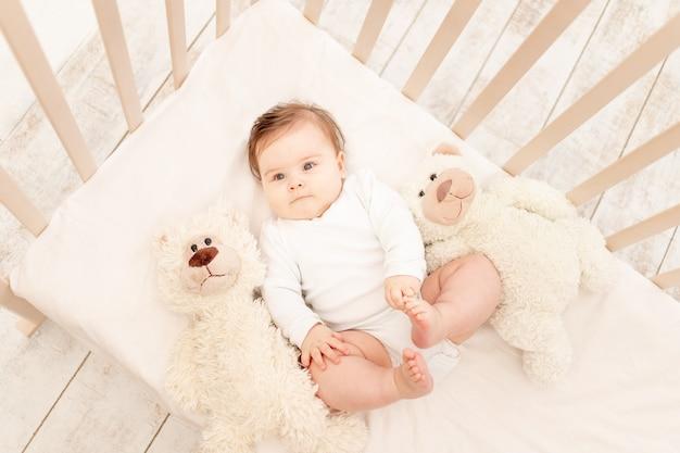 Малышке шесть месяцев в кроватке в белом боди с мишкой тедди.