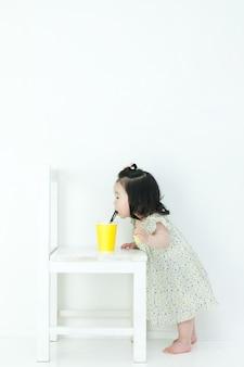아기가 컵에있는 숟가락과 이야기하고 있습니다.
