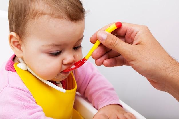 Ребенок открывает рот во время кормления. папина рука кормит малыша из силиконовой ложки