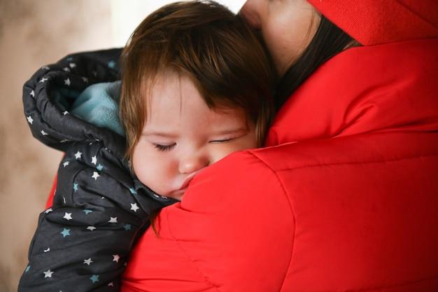 Ребенок спит на руках у мамы. после прогулки крупный план. спящий малыш. новорожденный ребенок спит на руках у мамы