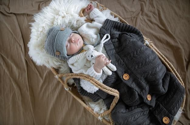 아기는 손잡이에 장난감이 달린 따뜻한 담요 아래 따뜻한 니트 모자에 고리 버들 요람에서 달콤하게 잠을 잔다.