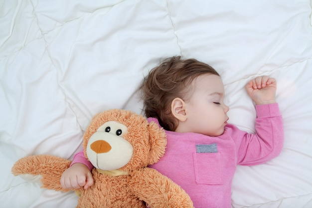 Малыш спит с игрушечным мишкой