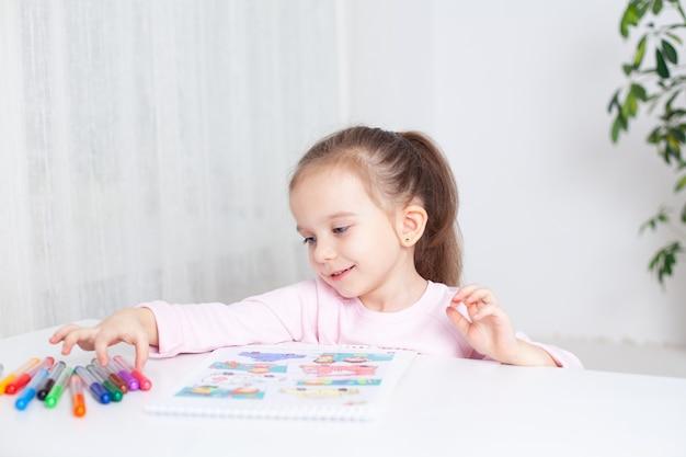 웃는 아기는 집과 유치원에서 아이들을 위한 수업을 그리기 위해 마커를 선택합니다