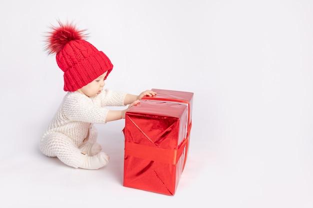 흰색 격리된 배경에 빨간 모자와 선물을 든 아기, 텍스트를 위한 공간, 새해와 크리스마스의 개념