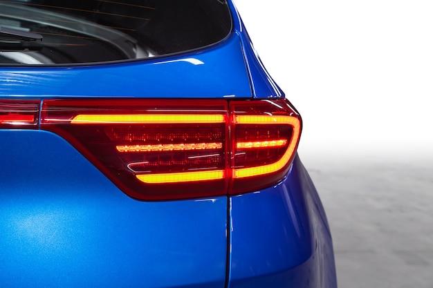 青い高価なクロスオーバー車の後ろ:バンパー、トランクリッド、後ろの白い背景のテールライト