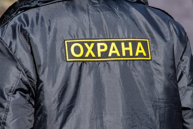 러시아어 security가 새겨진 검은색 재킷을 입은 남자의 등