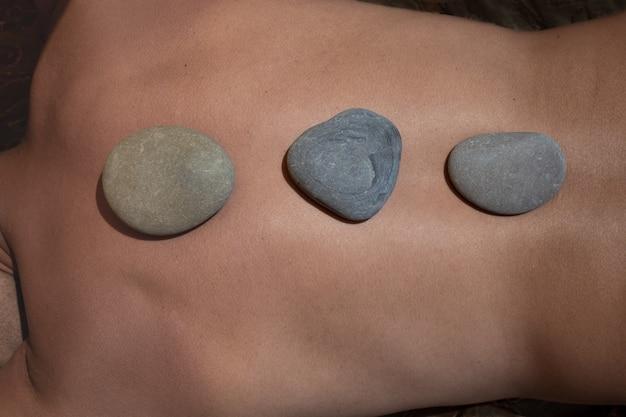 Спина мужчины, на которой расположены круглые камни по линии релаксации позвоночника.