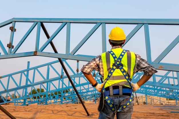 건설 현장의 높은 곳에서 작업하는 안전 장치와 안전 라인을 착용한 건설 노동자의 뒷모습. 프리미엄 사진