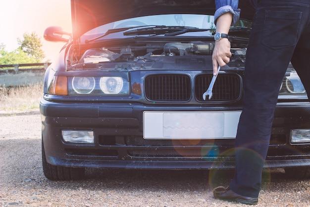 自動車修理のためのドライバーを持っている技術者の後ろ、ライトフレアで壊れた車。