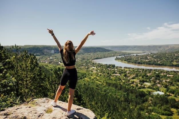 川や町を背景に山を旅する少女の背中