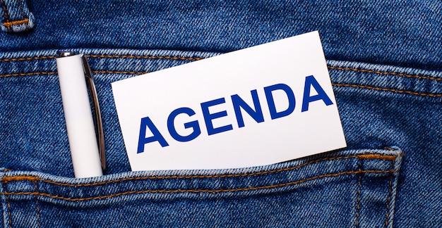 ブルージーンズの後ろのポケットには、白いペンと「agenda」というテキストの白いカードが入っています。