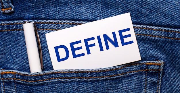 Задний карман синих джинсов содержит белую ручку и белую карточку с текстом define.