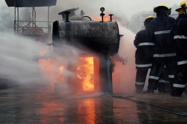 消防士のグループの背面図は、火を止めるのに役立ちました。